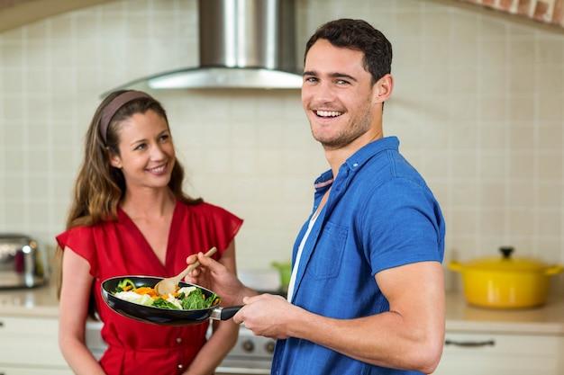 Par, segurando, panela, de, legumes, e, sorrindo, em, um ao outro, em, cozinha