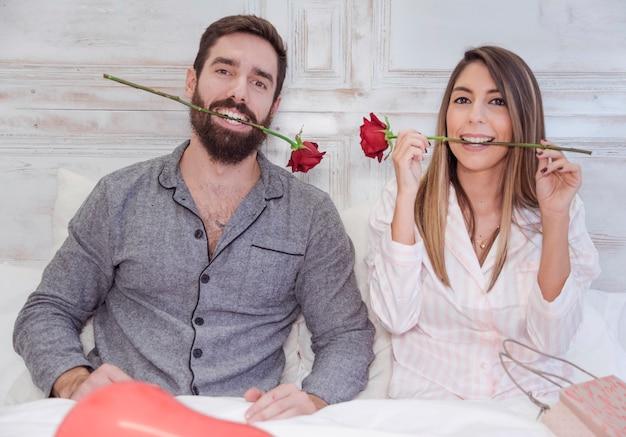 Par, segurando, rosas vermelhas, em, dentes