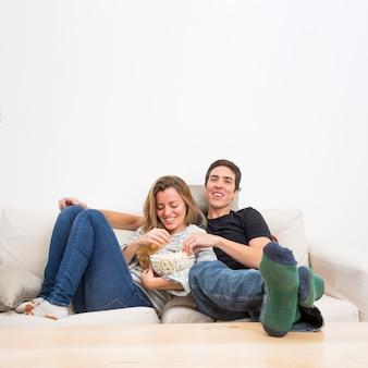 Par, sentando, ligado, sofá, comer, pipocas, em, tigela