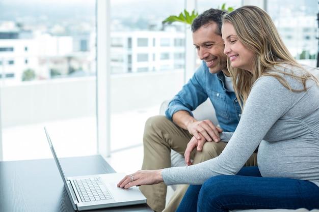 Par, sentando, ligado, sofá, e, usando computador portátil, em, sala de estar