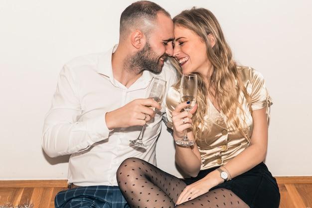 Par, sentar chão, com, champanhe, copos