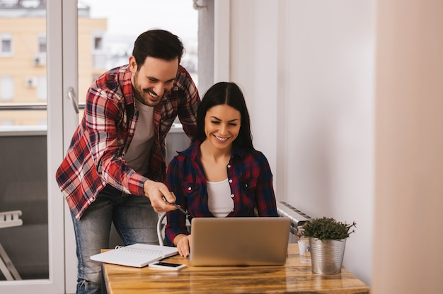 Par, trabalhando, junto, em, apartamento, homem apontando, ligado, computador