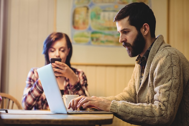 Par, usando computador portátil, e, telefone móvel