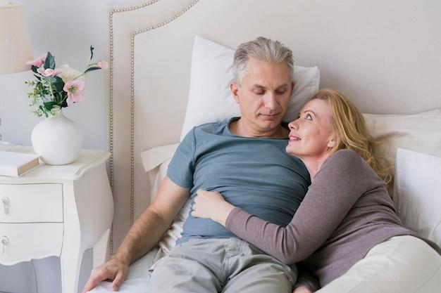 Par velho, abraçando, um ao outro, cama