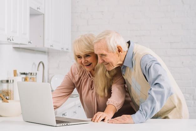 Par velho, com, laptop, em, cozinha