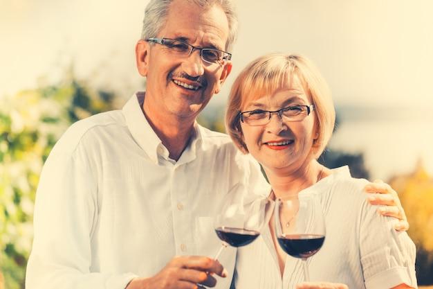 Par velho, desfrutando vinho tinto, ao ar livre