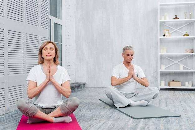 Par velho, meditar, com, orando, mãos, ligado, esteira yoga, casa