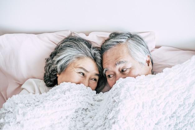 Par velho, mentindo cama, junto