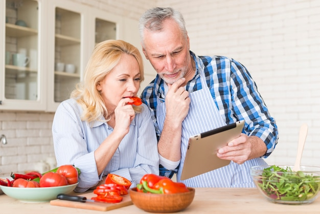 Par velho, olhar, tablete digital, enquanto, preparar, a, comida, cozinha