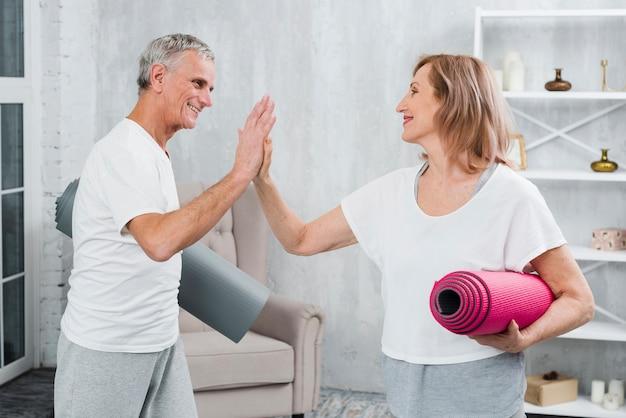 Par velho, segurando, ioga, tapetes, dar, alto cinco