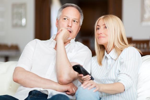 Par velho, sentar sofá, e, olhando tv