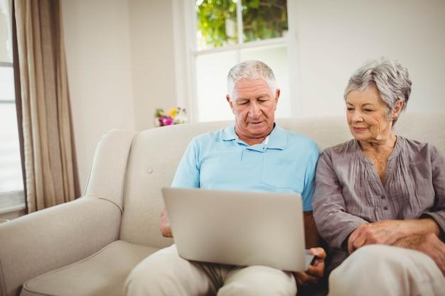 Par velho, sentar sofá, e, olhar, laptop, em, sala de estar