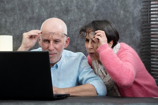 Par velho, usando computador portátil, eles, tendo, dificuldades, e, visão, problemas