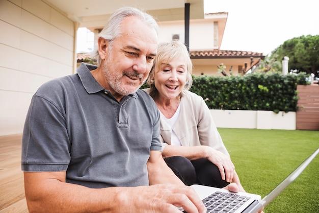 Par velho, usando computador portátil, em, jardim