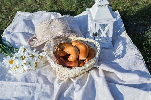 Para a cesta de vime tortas frescas, perto do chapéu, lanterna e um buquê de margaridas