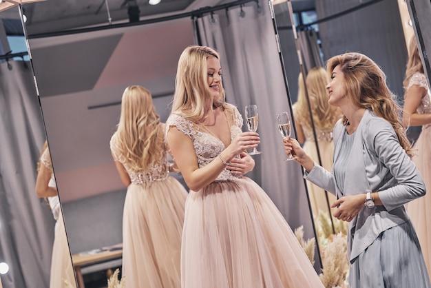 Para a noiva! moças atraentes brindando e sorrindo enquanto estão no provador