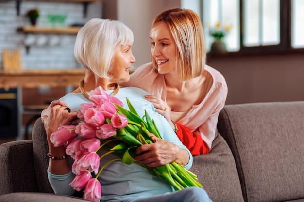 Para amar a mãe. atraente graciosa filha madura alegre com ternura olhando para uma mãe idosa sofisticada e sorridente, usando um suéter azul e segurando tulipas