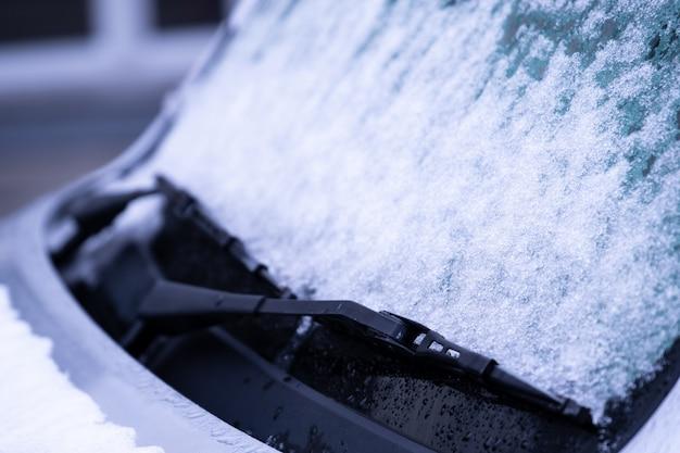 Para-brisa congelado do carro coberto com o gelo e a neve em um dia de inverno.