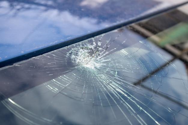 Pára-brisa quebrado com muitas rachaduras e pequenos pedaços de vidro, carro danificado