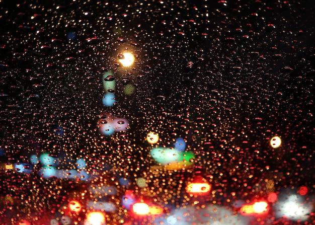 Pára-brisas do carro cheio de gotas de chuva com tráfego desfocado jam na rua urbana à noite