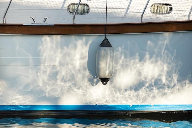 Pára-choque branco único pendurado no casco de um veleiro