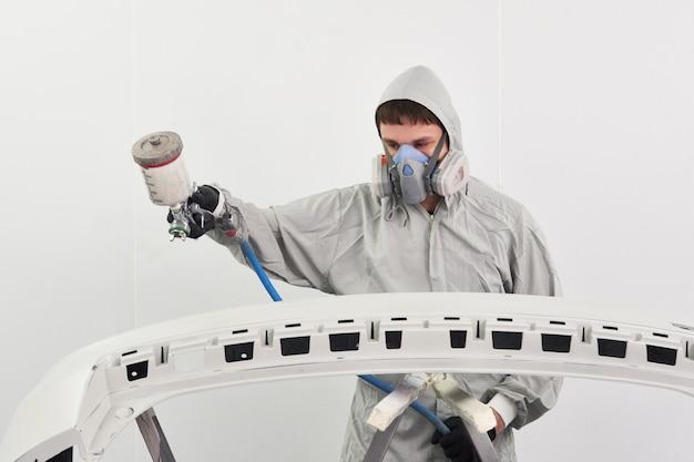Pára-choques de pintura mecânica de um carro com pulverizador na cabine de pintura no serviço de reparação automóvel