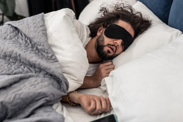 Para dormir melhor. belo homem moreno roncando enquanto dorme com uma máscara