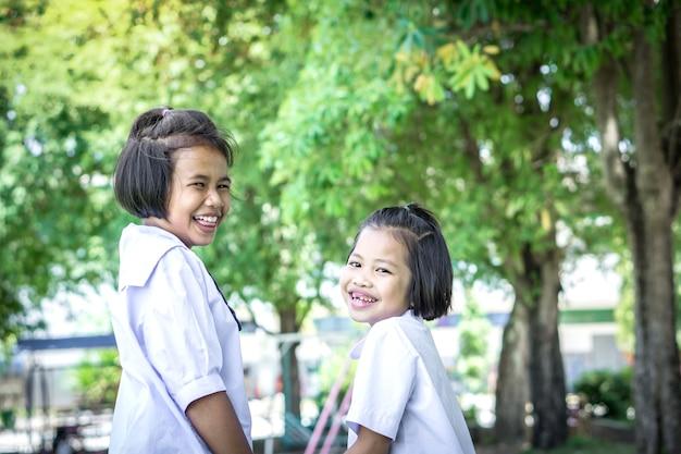 Para estudante asiática meninas crianças rindo na escola