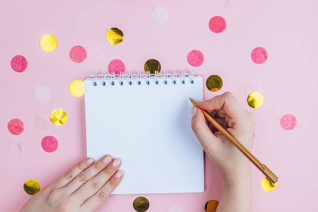 Para fazer a lista no bloco de notas em espiral no fundo rosa festivo. camada plana, vista superior.