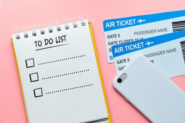 Para listar o conceito em um notebook perto de ingressos e um smartphone em uma parede rosa