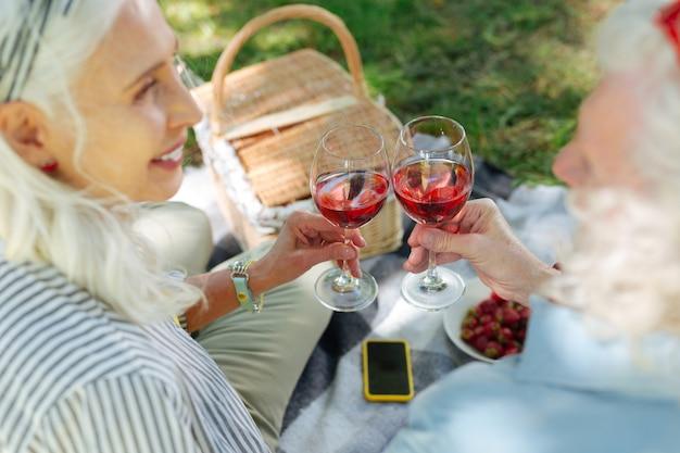Para nós. casal alegre e simpático torcendo por vinho enquanto celebra o aniversário