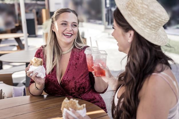 Para nós. mulheres felizes e alegres aplaudindo com copos de limonada enquanto comiam hambúrgueres no café