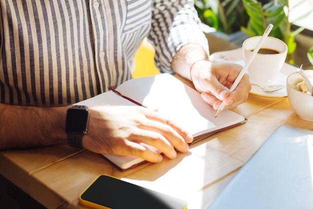 Para notas. vista superior de um caderno em cima da mesa enquanto é usado para fazer anotações