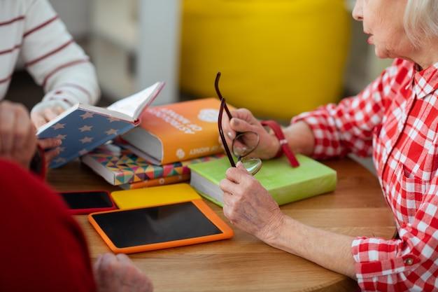 Para os olhos. close-up de óculos em mãos femininas durante a discussão sobre livros
