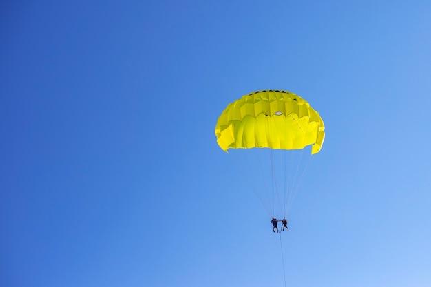 Pára-quedas amarelo com pessoas no céu azul
