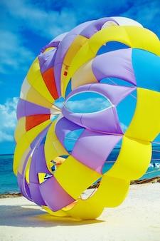 Pára-quedas colorido brilhante do arco-íris na praia atrás da água azul do oceano
