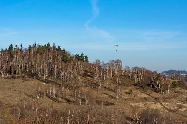 Pára-quedista no céu acima das árvores que crescem na encosta da montanha no início da primavera