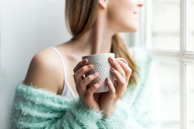 Para se aquecer na manhã fria. retrato de uma jovem mulher pela janela