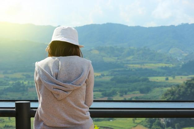 Para trás da menina asiática que senta e que presta atenção a uma vista natural.