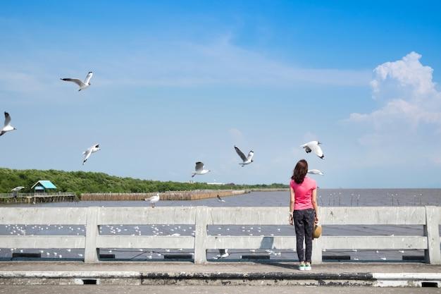 Para trás da mulher asiática que está no briedge com as gaivotas em bangpu, tailândia.