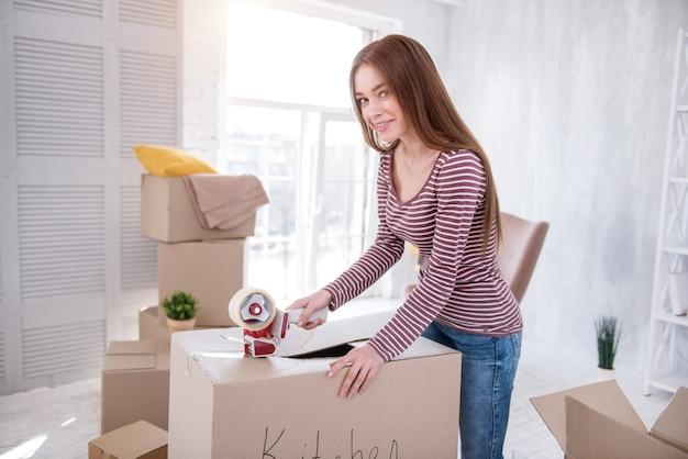Para uma nova casa. mulher bonita de cabelos escuros fechando a caixa com utensílios de cozinha com fita adesiva e posando para a câmera