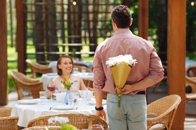 Parabenizando esposa. homem bonito de cabelos escuros usando uma elegante camisa rosa parabenizando sua esposa com a promoção