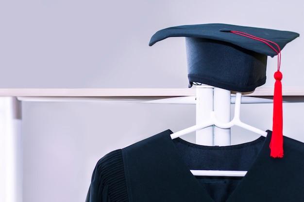 Parabenize graduado. vestido e chapéu negro da graduação no fundo branco.