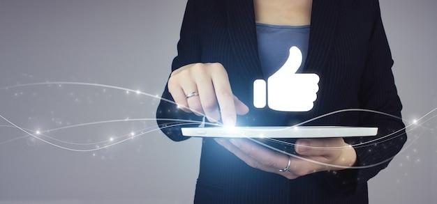 Parabéns, bom e gosto de conceito. tablet branco na mão da mulher de negócios com mão de holograma digital tombe ícone do sinal no fundo cinza. tumb up conceito.