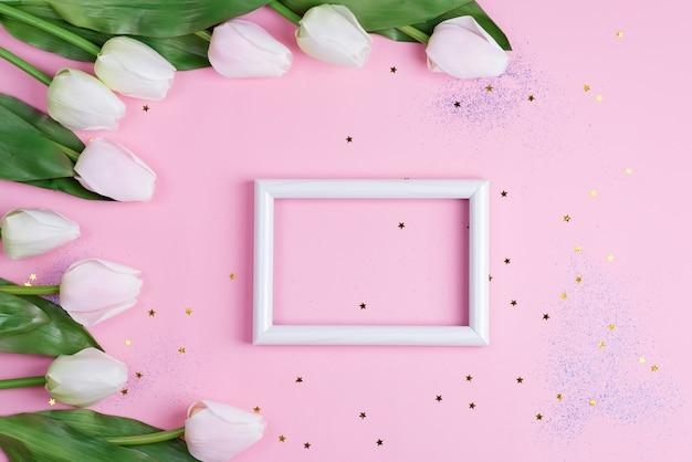 Parabéns cartão com moldura e borda de canto de flores tulipas brancas sobre um fundo rosa claro.