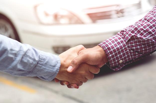 Parabéns. close-up do jovem empresário apertar as mãos do investidor entre dois colegas. um negócio de sucesso. Foto Premium