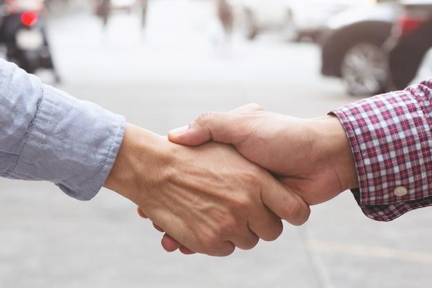 Parabéns. close-up do jovem empresário apertar as mãos do revendedor de automóveis no salão do automóvel após um negócio bem sucedido.