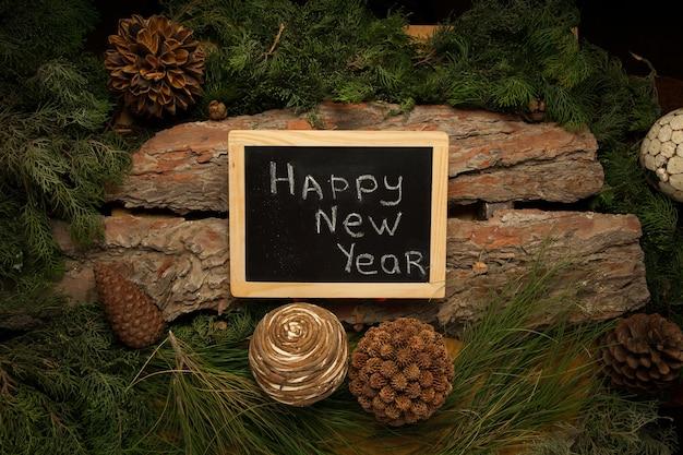 Parabéns com ano novo na lousa com ramos de pinheiro e pinhas