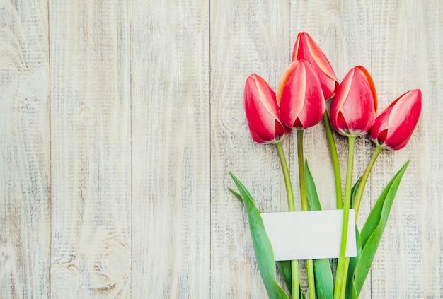 Parabéns e tulipas sobre um fundo claro. foco seletivo.