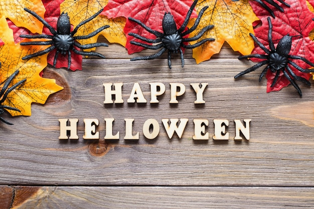 Parabéns feliz halloween. letras de frases rodeadas por folhas de bordo e aranhas
